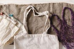 Sacos reusáveis naturais de Eco para comprar, configuração lisa no backg rústico foto de stock