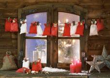Sacos, velas e estrelas do Natal na placa de janela Imagens de Stock