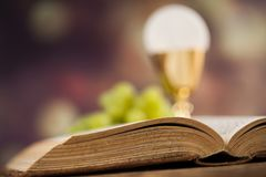 Holy communion a golden chalice with grapes and bread wafers. Sacrament of communion, Eucharist symbol royalty free stock image