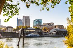 Sacramento`s skyline and waterfront. Framed by tree branches, as seen from the banks of Sacramento river of a sunny morning; California royalty free stock photo