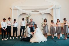 SACRAMENTO, USA - MAY 12 th 2018: Bride and groom pray and receive blessings in the church building.  stock photography