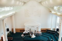 SACRAMENTO, USA - MAY 12 th 2018: Bride and groom pray and receive blessings in the church building.  stock photo