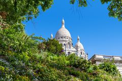 Sacre-Coeur Basilica and green flowerbed in Paris. Green flowerbed with flowers as famous Sacre-Coeur Basilica on background under blue sky in Paris, France Stock Images