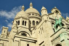Sacre Coeur cathedral architectural features. A portion of the Sacre Coeur cathedral in Paris, showing architecture elements and a statue Royalty Free Stock Image