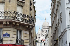 Sacre Coeur down street in Paris, France. Sacre Coeur, the Church of the Sacred Hearts, framed by buildings along street in Paris, France Royalty Free Stock Photography