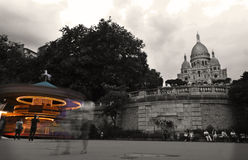 Sacre Coeur: monochrome Montmartre Fairground with a colourful carousel Royalty Free Stock Images