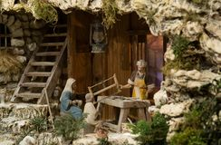 Sacred family. A manger, depicting the sacred family with St.Joseph working as a carpenter, and Jesus as a child Royalty Free Stock Image