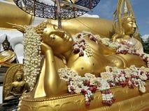 Sacred fragrant flowers on recline Buddha sculpture Stock Photo