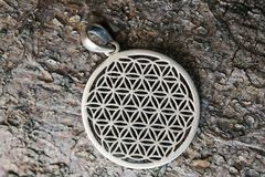 Sacred geometry flower of life silver pendant. On wooden background stock images
