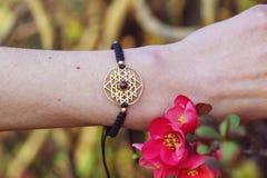 Sacred geometry metal natural stone bracelet. On female wrist stock photo