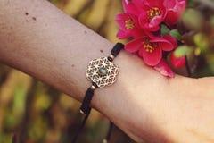 Sacred geometry metal natural stone bracelet. On female wrist stock image