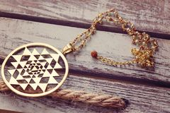 Sacred geometry pendant necklace. On wooden background stock image