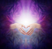 Sacred Healing Energy. Female hands emerging from a deep purple background making a heart shape over a bright glowing energy manifestation with plenty of copy royalty free illustration