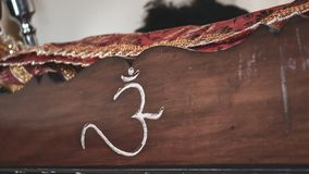 Sacred Hindu word `OM` in Sanskrit carved into a wood stand for the scriptures. royalty free stock image