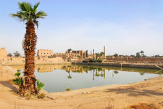 Sacred Lake in Karnak. The Karnak Temple Complex comprises a vast mix of decayed temples, chapels, pylons, and other buildings. Building at the complex began in Royalty Free Stock Photo