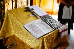 Sacred lectern in the church decorated with golden friezes and ornaments, church interior with bible on reading-desk or lectern.  stock photos