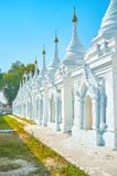 The sacred place in Mandalay, Myanmar. The Kuthodaw Pagoda boasts numerous white stupas with Trapitaka texts on the tablets inside, Mandalay, Myanmar royalty free stock image