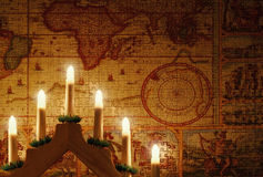 Sacred puzzle of the world. Candles on a background of a puzzled world Stock Photography