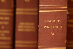 Sacred Writings. Closeup, selective focus image of an old worn book spine. Out of focus additional books in background Royalty Free Stock Photography