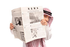 Sacred young Arab hiding behind a newspaper Stock Photos