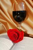 The sacrifice and blood of Jesus. Red rose on the opened Bible next to the glass of red wine evokes the sacrifice and suffering of Jesus stock photos