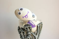 Sacrifice concept joke. Eggs. With a funny painted face lie in a glass with skulls. Photo for your design Royalty Free Stock Photo