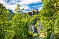 Sacro Monte of Varese Santa Maria del Monte, Italy. Via Sacra that leads to medieval village in the background. Stations of the cross with the tenth chapel and Stock Photography