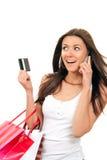 Sacs à provisions de femme, parler par la carte de crédit au téléphone Images stock