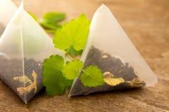 Sacs à thé avec la mélisse (menthe) images stock
