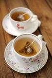 Sacs à thé de pyramide brassés dans des deux tasses Image libre de droits
