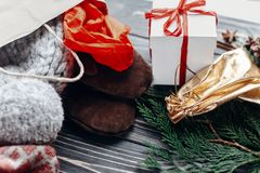 Sacs actuels avec des vêtements et des cadeaux sur le fond rustique en bois Image libre de droits