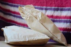 Sacs avec des petits pains sur une surface en bois sur un fond de tissu image libre de droits