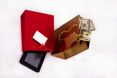 Sacs de cadeau avec le comprimé et les dollars Photo stock