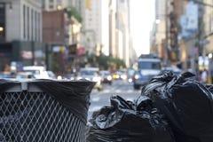 Sacs de déchets avec le trafic trouble à l'arrière-plan dans des environmen urbains Images stock