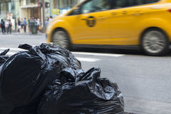 Sacs de déchets avec le trafic trouble à l'arrière-plan dans des environmen urbains Image stock