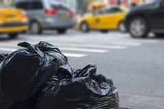 Sacs de déchets avec le trafic trouble à l'arrière-plan dans des environmen urbains Image libre de droits