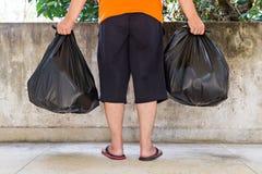 Sacs de déchets de transport de jeune homme Images libres de droits