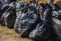 Sacs de déchets noirs, complets et attachés se tenant ensemble sur la rue, Photo stock