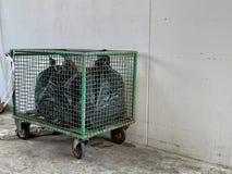 Sacs de déchets noirs disposés dans un chariot vert sur le plancher de ciment près du mur blanc, chariot de déchets pour la réuti image libre de droits