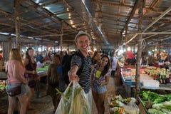 Sacs de sourire heureux de prise de couples avec des légumes chez l'homme gai et la femme de marché en plein air faisant des empl Image stock