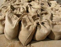 Sacs de toile de jute complètement du sable Photos stock