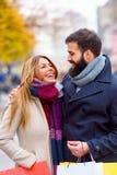 Sacs de transport de beaux jeunes couples affectueux et avoir plaisir à faire des emplettes ensemble Photographie stock libre de droits