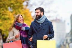 Sacs de transport de beaux jeunes couples affectueux et avoir plaisir à faire des emplettes ensemble Image libre de droits