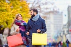 Sacs de transport de beaux jeunes couples affectueux et avoir plaisir à faire des emplettes ensemble Photos stock