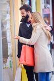 Sacs de transport de beaux jeunes couples affectueux et avoir plaisir à faire des emplettes ensemble Photo libre de droits