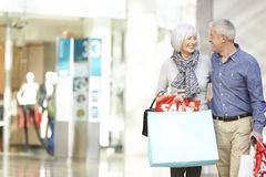 Sacs de transport de couples supérieurs heureux dans le centre commercial photos libres de droits