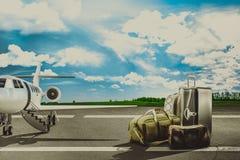 Sacs de voyage dans l'aéroport et l'avion de ligne Photo stock