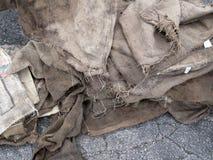 Sacs grunges à toile de jute sur l'asphalte Photos stock