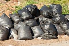 Sacs noirs remplis de déchets au bord de la route photo stock