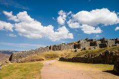 Sacsayhuaman avec la belle route de nuages à Cusco Images stock